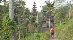 Tourists walking towards Puru Gunung Lebay temple,Ubud,Bali,Indonesia Stock Footage