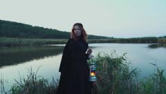 young female dressed in old-fashioned clothes standing near the lake with lamp - stock footage