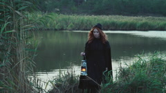 female dressed in old-fashioned clothes holding a lamp walking near the lake - stock footage
