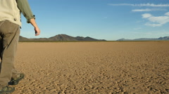 A man walking in a harsh desert landscape Stock Footage