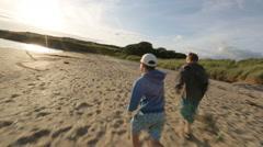Kids Running on Beach into Sun Stock Footage