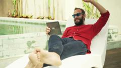 Young, happy man on sunbed by pool chatting on tablet computer Stock Footage