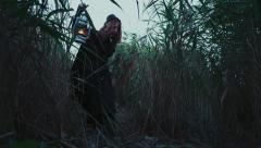 female dressed in old-fashioned clothes wading through bushes with a lamp - stock footage