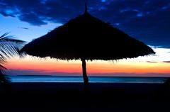 Silhouette of Parasol on a beach over Sunset Stock Photos