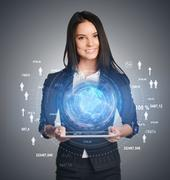 Young girl holding tablet in hands of a virtual digital globe and icons on sides - stock photo