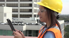 Female contractor at construction site using an ipad/tablet - stock footage