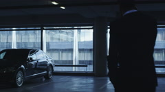 Businessman in a suit is walking towards an executive car in a garage parking Stock Footage