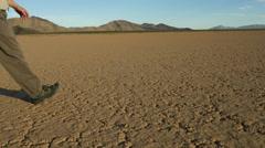 Man walking on a desert playa, dead soil - stock footage