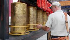 Western Male Tourist Turns Tibetan Prayer Wheels Stock Footage