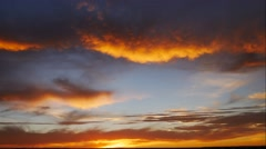 Beautiful color filled time lapse of the setting sun and large clouds. Stock Footage