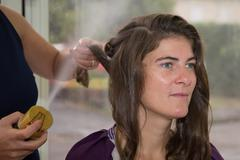 Stock Photo of Stylist pinning up a woman's hairstyle at a beauty saloon
