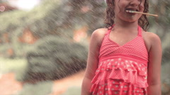 A cute little girl eating a lollipop being sprayed with a hose - stock footage