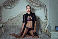 Girl erotic lingerie flirting on bed in the bedroom. - stock photo