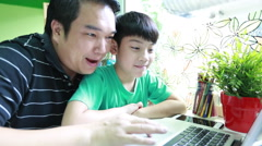 Asian happy Dad is teaching her son Using Laptop in living room Stock Footage