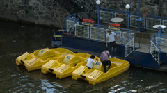 Couple floating on Vltava River on a yellow pedal boat, Prague Stock Footage