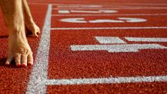 Track runner putting his hands at starting line Stock Footage