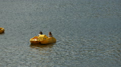 Two yellow pedal boats floating on Vltava River, Prague Stock Footage