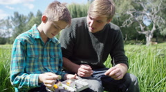 4K Man and young boy together on fishing trip, putting fishing flies on the hook Stock Footage