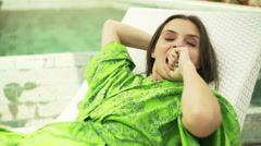 Woman waking up and yawning on sunbed by pool Stock Footage