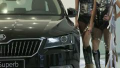 Spokesmodels stands next to new car Skoda Superb during presentation in showroom Stock Footage