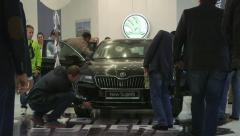 Visitors around new car Skoda Superb model 2015 during presentation in showroom Stock Footage