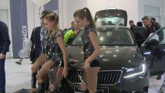Spokesmodels poses beside new car Skoda Superb 2015 in the dealership showroom - stock footage