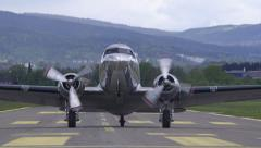Douglas DC-3 old propeller airplane taxiing towards camera on runway Stock Footage