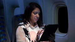 Young woman on plane at night using an ipad/tablet Stock Footage