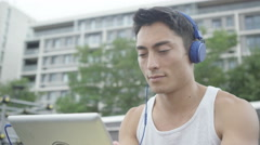 4K Asian man in outdoor urban environment with headphones and tablet computer - stock footage