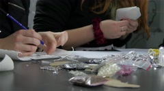 Girl makes pattern with pen and other girls sewing, making jewelry, materials. Stock Footage