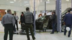 Car dealer presents new model Skoda Superb 2015 in dealership showroom Stock Footage