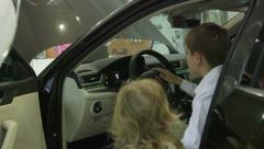 Child at the wheel of new car Skoda Superb 2015 in dealership showroom Stock Footage