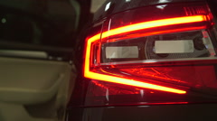 Tail light of new car Skoda Superb 2015 in dealership showroom closeup Stock Footage