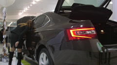 Visitors view a new car Skoda Superb model 2015 in dealership showroom Stock Footage