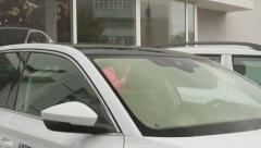 Female customer looking inside new car in front of dealership showroom Stock Footage