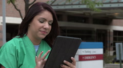 Nurse using an ipad/tablet outside a hospital Stock Footage