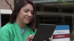 Young health care professional using an ipad/tablet near a hospital Stock Footage