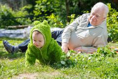 Senior man and baby on nature Stock Photos