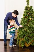 boy decorating the christmas tree with her father at home - stock photo