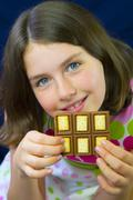 Beautiful teenage girl eating chocolate - stock photo