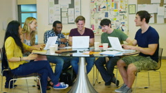 4K Mixed ethnicity student group working together in college - stock footage