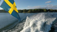National Flag of Sweden on stern of boat with water wake and wash Stock Footage