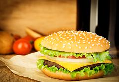 Delicious hamburger on brown paper on a wooden tabletop Stock Photos