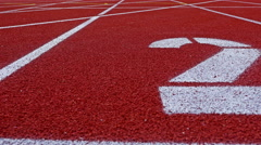 Slow dolly of a number 2 on a running track, counter number two Stock Footage