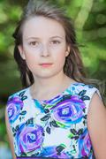 Cute preteen long hair girl posing on natural green background Stock Photos