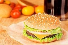 Delicious hamburger on brown paper on a wooden tabletop - stock photo