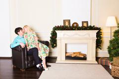 Happy young couple near Christmas tree at home Stock Photos