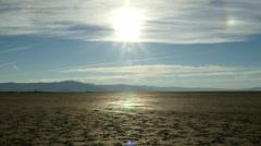 Man walks in hot sun in harsh desert - stock footage