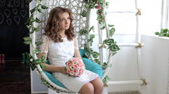 Bride with bouquet sitting in a chair Stock Footage