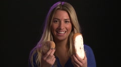 Pretty Blond Eats Donuts, Caucasian, black background Stock Footage